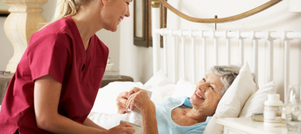 Health Visitor Talking To Senior Woman Patient In Bed